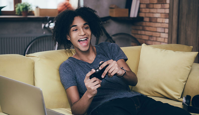 Ready to Play: No Driver Needed. A teenager is playing console game on a couch and using LGHD2 to capture his gameplay.